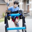 Six year old disabled boy walking in walker down the street - Stok fotoğraf