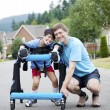 Foto Stock: Father kneeling next to disabled son standing in walker