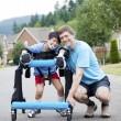 babasının yanında diz çökmüş walker duran oğlu devre dışı. — Stok fotoğraf