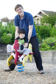 Father helping disabled son play at playground — Stock Photo