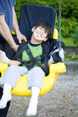 Disabled five year old boy in handicap swing — Stock Photo