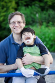Father holding disabled son at playground — Stock Photo
