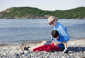 Father sitting on beach playing with disabled son — Stock Photo