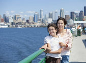 Two sisters on ferry deck with Seattle skyline in background — Stock Photo