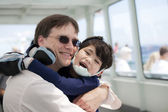 Father hugging disabled son as they ride a ferry boat — Stock Photo