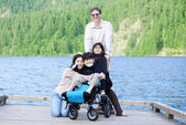 Disabled boy in wheelchair surrounded by family on lake pier — Stock Photo