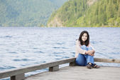Young teen girl sitting quietly on lake pier, relaxing — Stock Photo