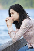 Young teen girl sitting quietly on lake pier, praying — Stock Photo