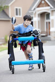 Six year old disabled boy walking in walker down the street — Foto de Stock