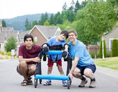 Disabled boy in walker surrounded by father and older brother — Stock Photo