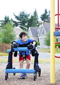 Disabled boy in walker walking up to a handicap inaccessible pla — Stock Photo