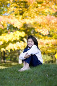 Little girl hugging knees sitting on lawn against bright autumn — Stock Photo