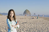 Beautiful biracial girl on sandy beach near Haystack Rock — Zdjęcie stockowe