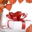 White present with red ribbons on a dinner plate — Stock Photo