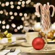Candy canes and ornaments on table — Stock Photo
