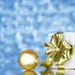 Gold present and ornament on blue shining background — Stock Photo