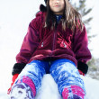 Little girl sitting on pile of snow in winter — Stock Photo #17742661