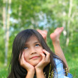 Foto Stock: Little biracial girl lying on grass, thinking