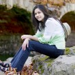Foto Stock: Biracial teen girl relaxing on rocks by stone bridge