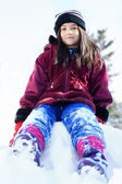 Little girl sitting on pile of snow in winter — Stock Photo