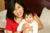 Asian mother sitting with baby boy on bed, smiling — Stock Photo