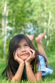 Little biracial girl lying on grass, thinking — Stok fotoğraf