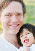 Handsome father smiling with his infant son, outdoors — Stock Photo