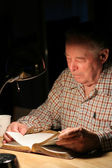 ELderly man reading Bible with lamp at night — Stock Photo