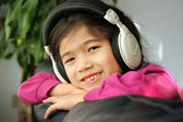 Six year old listening to music — Stock Photo