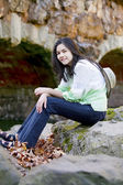 Biracial teen girl relaxing on rocks by stone bridge — 图库照片