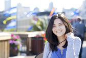 Young biracial teen girl smiling outdoors, sunny background — Foto Stock
