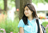 Young teen girl standing with backpack by tree, smiling. — Stock Photo