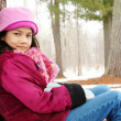 Child sitting under tree outdoors in winter — Stock Photo