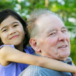 Little girl hugging her grandfather outdoors, diversity — Stock Photo