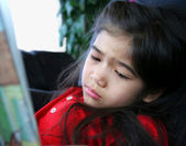 Child sadly reading a story — Stock Photo