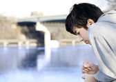 Teen boy sadly looking out over river, thinking — Stock Photo