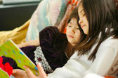Two girls reading a book — Stockfoto