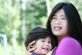 Asian mother lovingly holding her son — Stock Photo