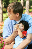 Father feeding baby a bottle in the park — Stock Photo