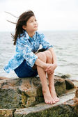 Nine year old girl sitting by lake — Stock Photo