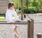 Little girl sitting on top of parallel bars at playground — Stock Photo