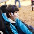 Stock Photo: Sisabled boy sitting in wheelchair while playing on playground