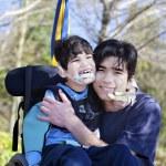 küçük Engelli çocuğa tekerlekli sandalye sevmek büyük kardeşi açık havada — Stok fotoğraf #24711403