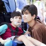 Ağabeyim tekerlekli sandalyede engelli çocuk bakımı — Stok fotoğraf #24711513