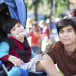 Ağabeyim tekerlekli sandalyede engelli çocuk bakımı — Stok fotoğraf #24711515
