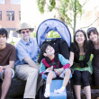 Photo: Father sitting with his biracial children and disabled son