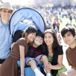 Large multiracial family in crowd with disabled child in wheelch — Stock Photo