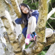 Stock Photo: Young girl sitting in birch tree, smiling