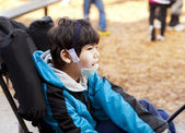 Sisabled boy sitting in wheelchair while playing on playground — Stock Photo