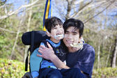 Little disabled boy in wheelchair hugging older brother outdoors — Stock Photo